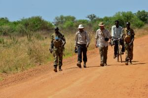 Lev and Boston walk with SPLA officers and a porter on the road North from Juba heading towards Terekeka.  (Tom McShane Photography)